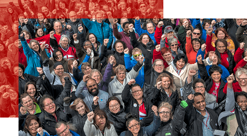 A large group of AUPE members stand together at the 2018 Labour School, smiling and laughing, with their fists in the air in solidarity.