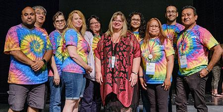 Members of Alberta Union of Provincial Employees (AUPE)'s Humans Rights Committee stand together at AUPE's Annual Convention, smiling, most of them wearing matching tie-dyed shirts--Vice-President Karen Weiers is standing in the middle of the group.