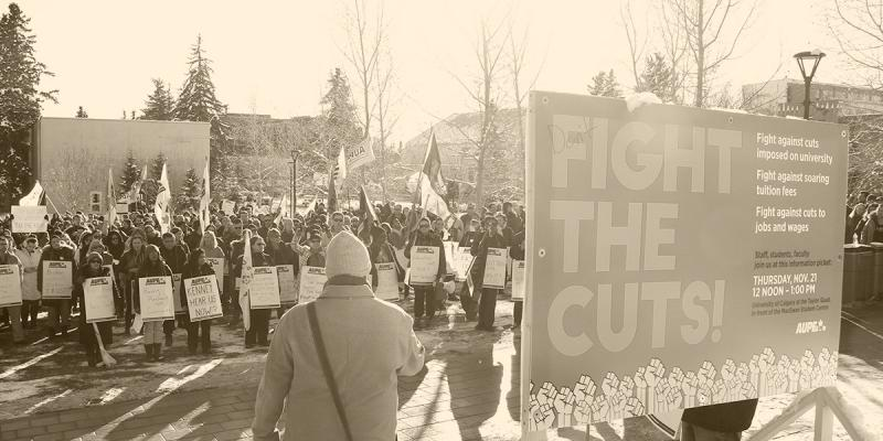 "AUPE rally with member holding a large sign that reads ""FIGHT THE CUTS!"""