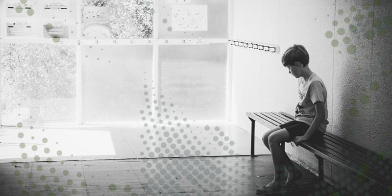 Black and white image of a solemn child sitting alone on a bench with head down